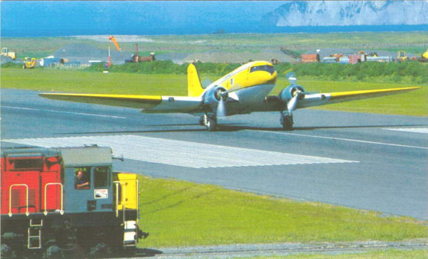 New Zealand Rail freight train waits for a Fieldair DC-3 topdresser (crop duster) to clear the runway